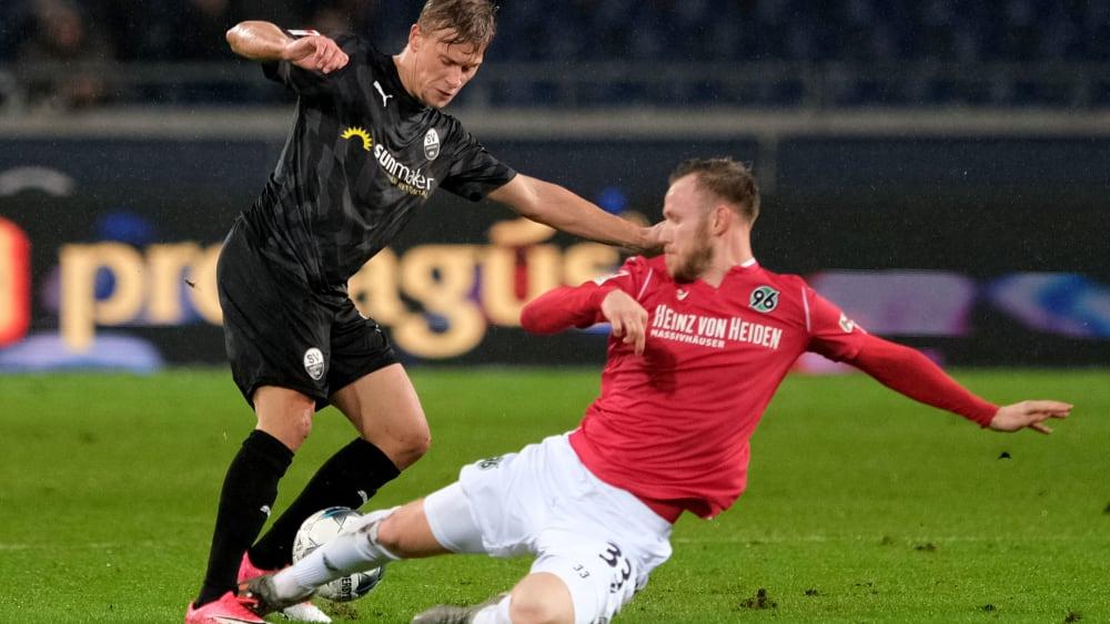 Hannovers Cedric Teuchert grätscht gegen Sandhausens Julius Biada zum Ball.