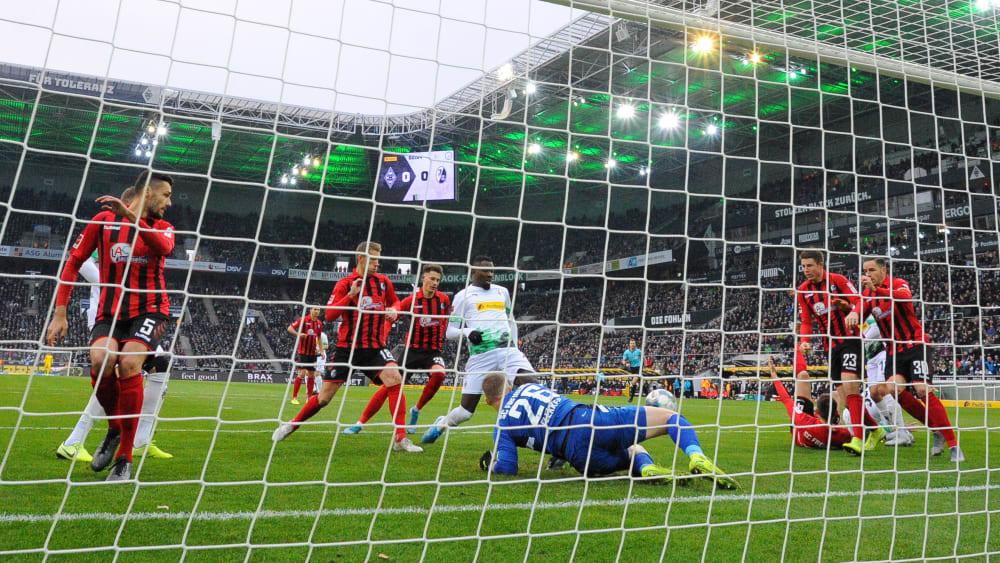 Freiburg-Keeper Mark Flekken (am Boden) wehrt kurz ab, Gladbachs Marcus Thuram (Mitte) staubt ab.