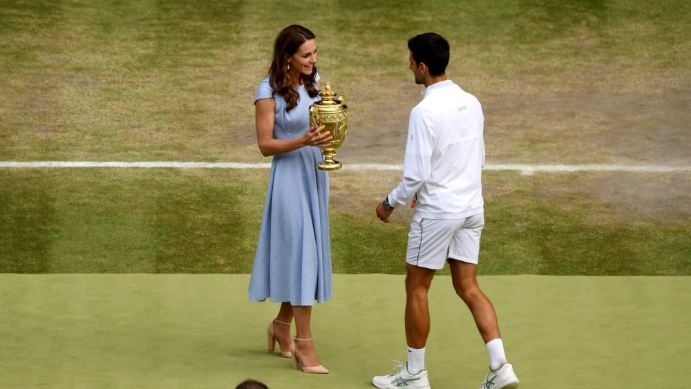 Novak Djokovic bekommt die Trophäe von Herzogin Kate überreicht.