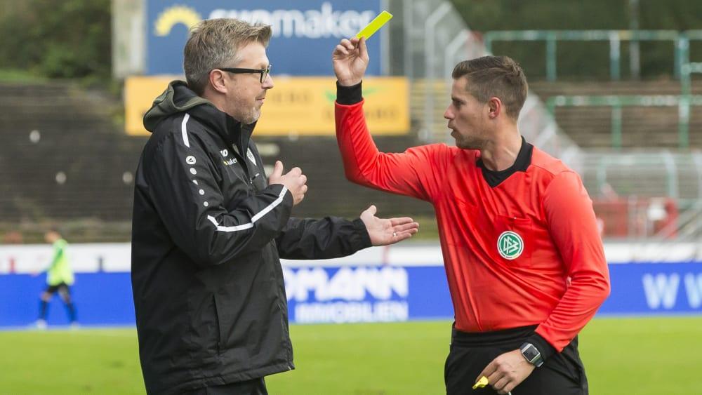 Schiedsrichter Robert Kempter (rechts) zeigt Münster-Coach Sven Hübscher die gelbe Karte.