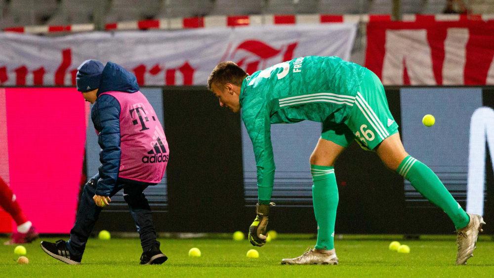 Bayern-II-Keeper Christian Früchtl hilft beim Aufräumen der von Bayern-Fans auf das Spielfeld geworfenen Tennisbälle.