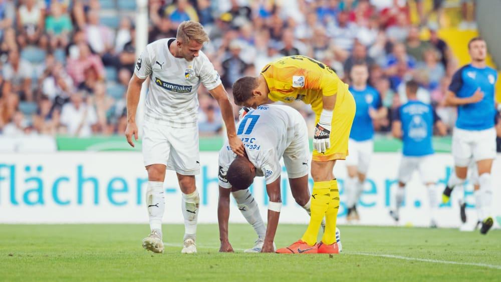 Pierre Fassnacht (li.) und Jo Coppens versuchen Marian Sarr nach dessen 2. Eigentor zum 2:1 für Ingolstadt aufzumuntern,