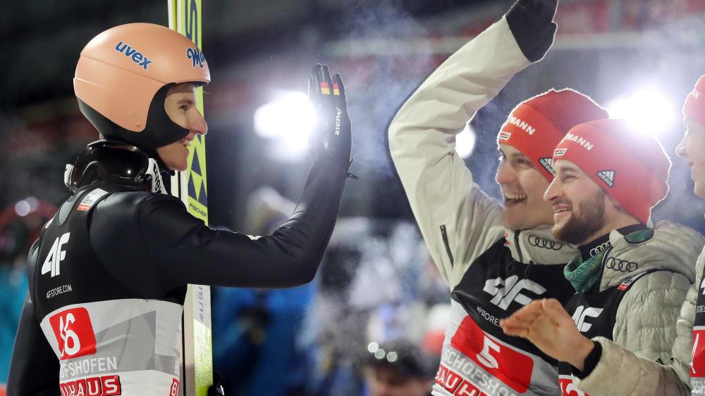 Karl Geiger lässt sich von Stephan Leyhe und Markus Eisenbichler feiern.