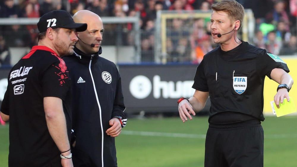 Schiedsrichter Christian Dingert (rechts) zeigt Paderborns Trainer Steffen Baumgart die Gelbe Karte.